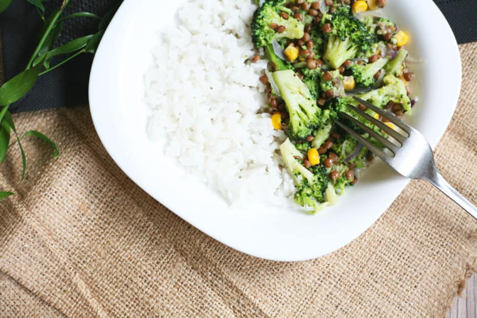 Close-up of a white plate and fork with broccoli and lentil stir fry on rice.