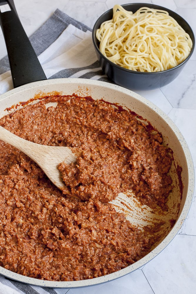 White frying pan with cauliflower walnut mince in vegan bolognese sauce