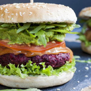 Close-up of a beet burger with layers like burger bun, lettuce, purple patty, tomato slice, green puree, arugula and bun on the top