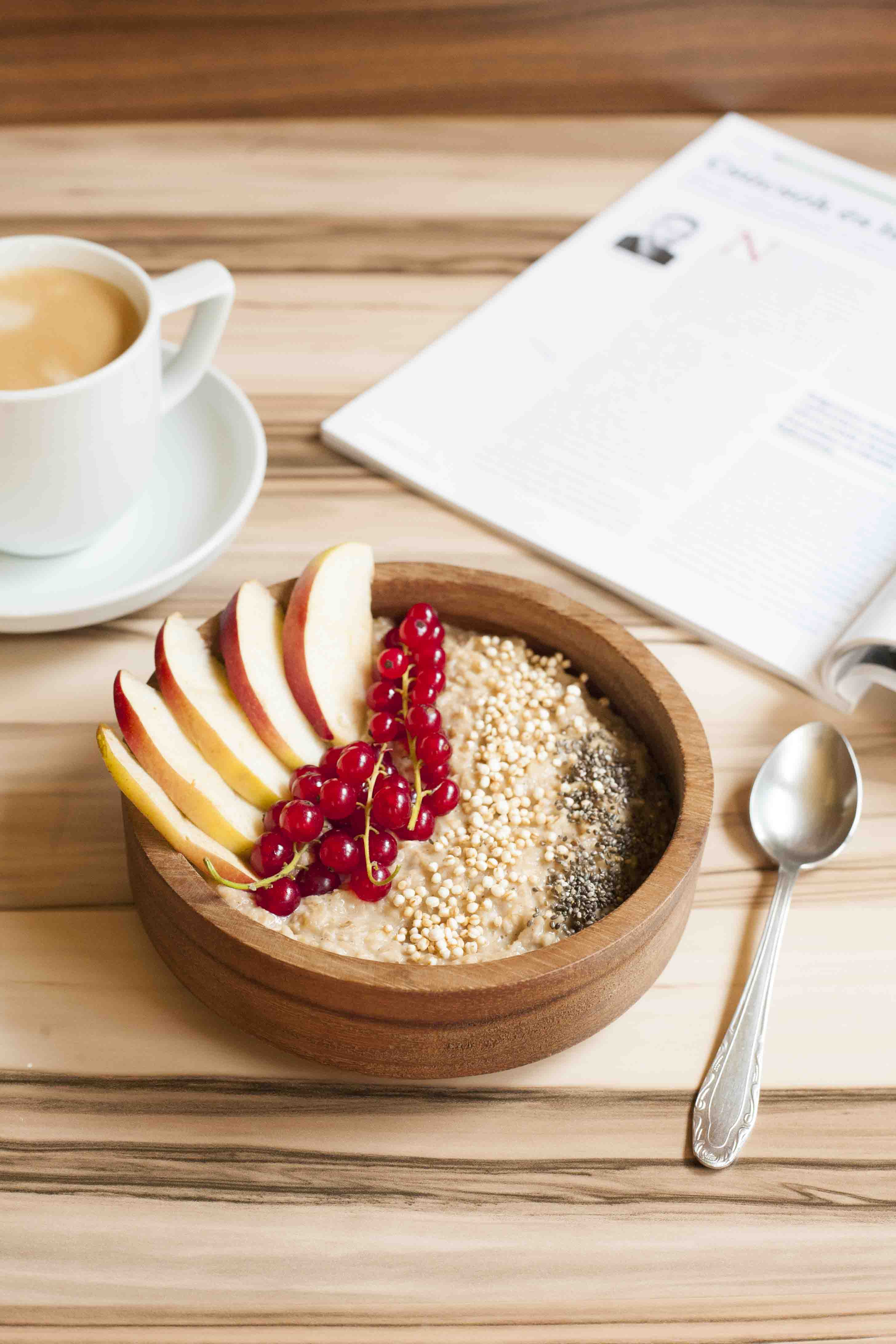 Bowl of Vegan Apple Cinnamon Oatmeal made on stove top - topped with apple slices, red currant, chia seeds and puffed quinoa