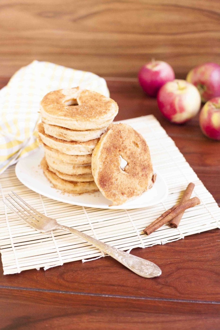 Stack of cinnamon fried battered apple rings on a white plate.