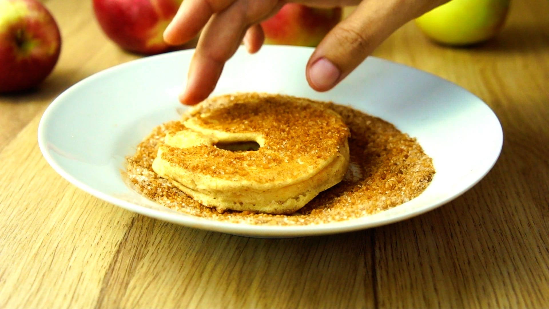 White plate sprinkled with cinnamon sugar and a fried apple ring is coated using a hand.