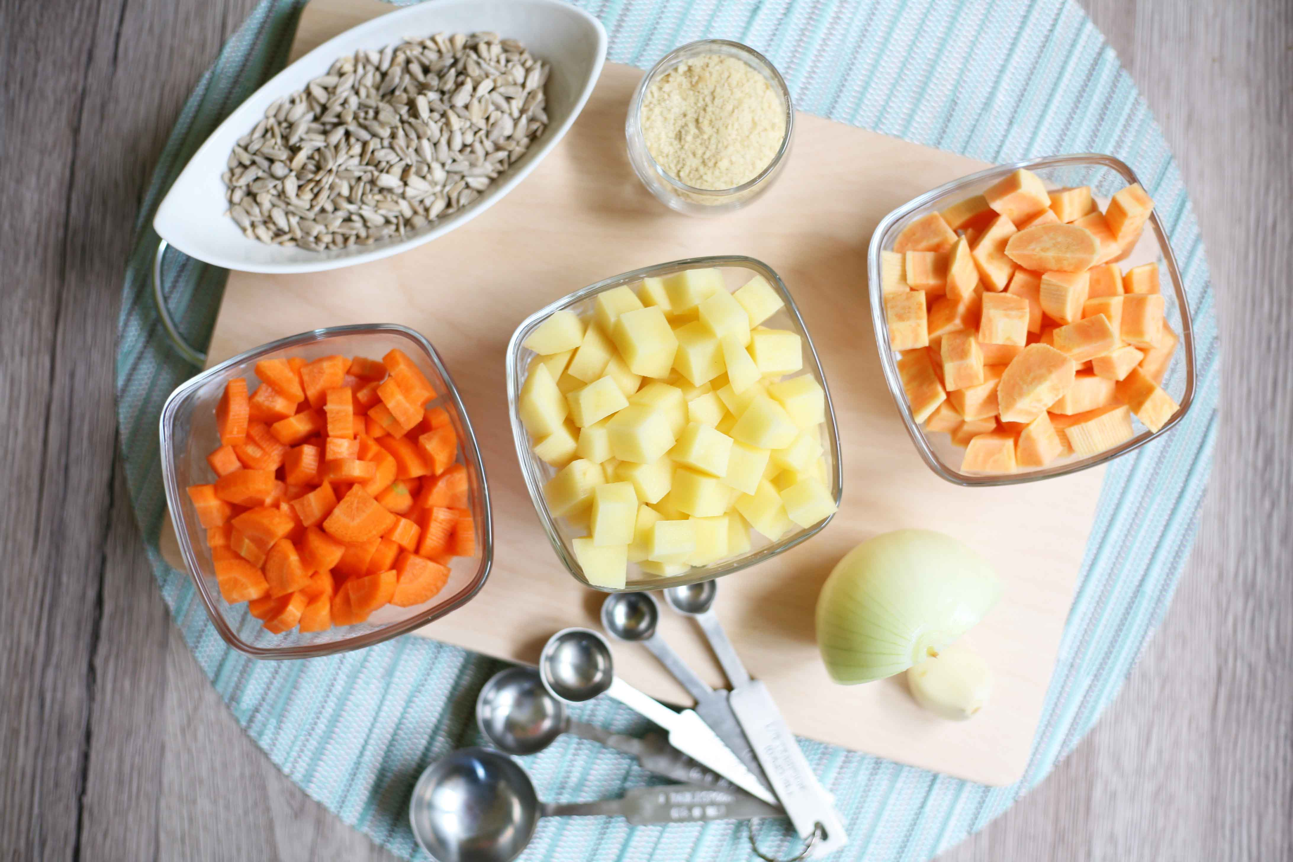 All ingredients measured in small bowls to make Easy Vegan Nut-free Nacho Cheese Sauce: diced carrots, diced sweet potato, diced potato, sunflower seeds, half onion, clove of garlic and nutritional yeast