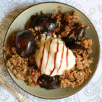 Small green plate with a serving of brown crumble, plum and a scoop of vanilla ice cream.
