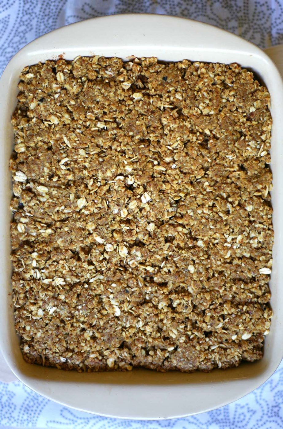 A baking dish with brown crunchy crumble topping nicely flattened into the dish on one layer.