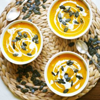 3 small bowl of pumpkin soup sprinkled with pumpkin seeds, chia seeds and dairy-free cream poured on top.