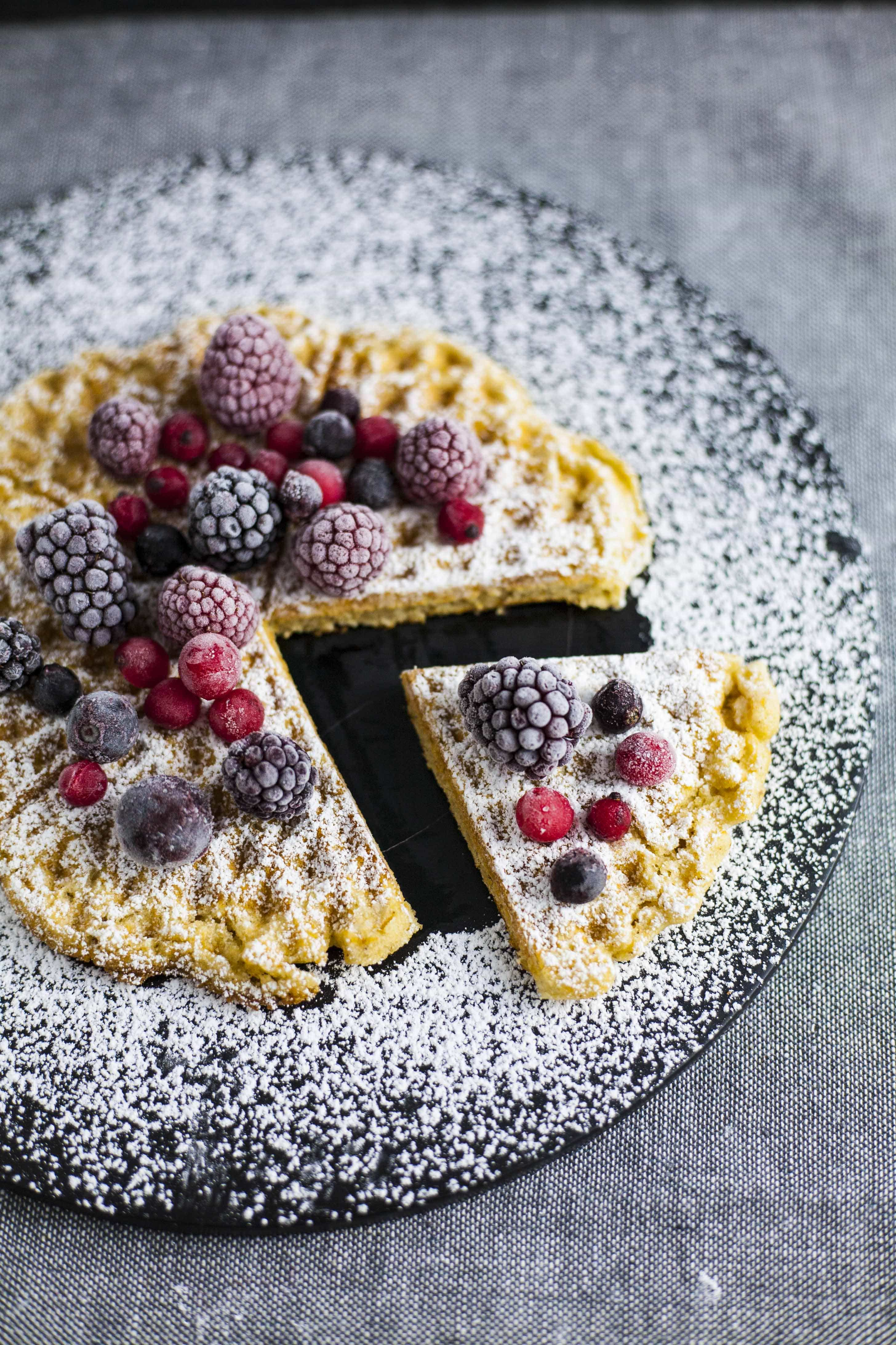 Crispy vegan waffle made in five-of-hearts waffle iron. Topped with berries and powdered sugar.