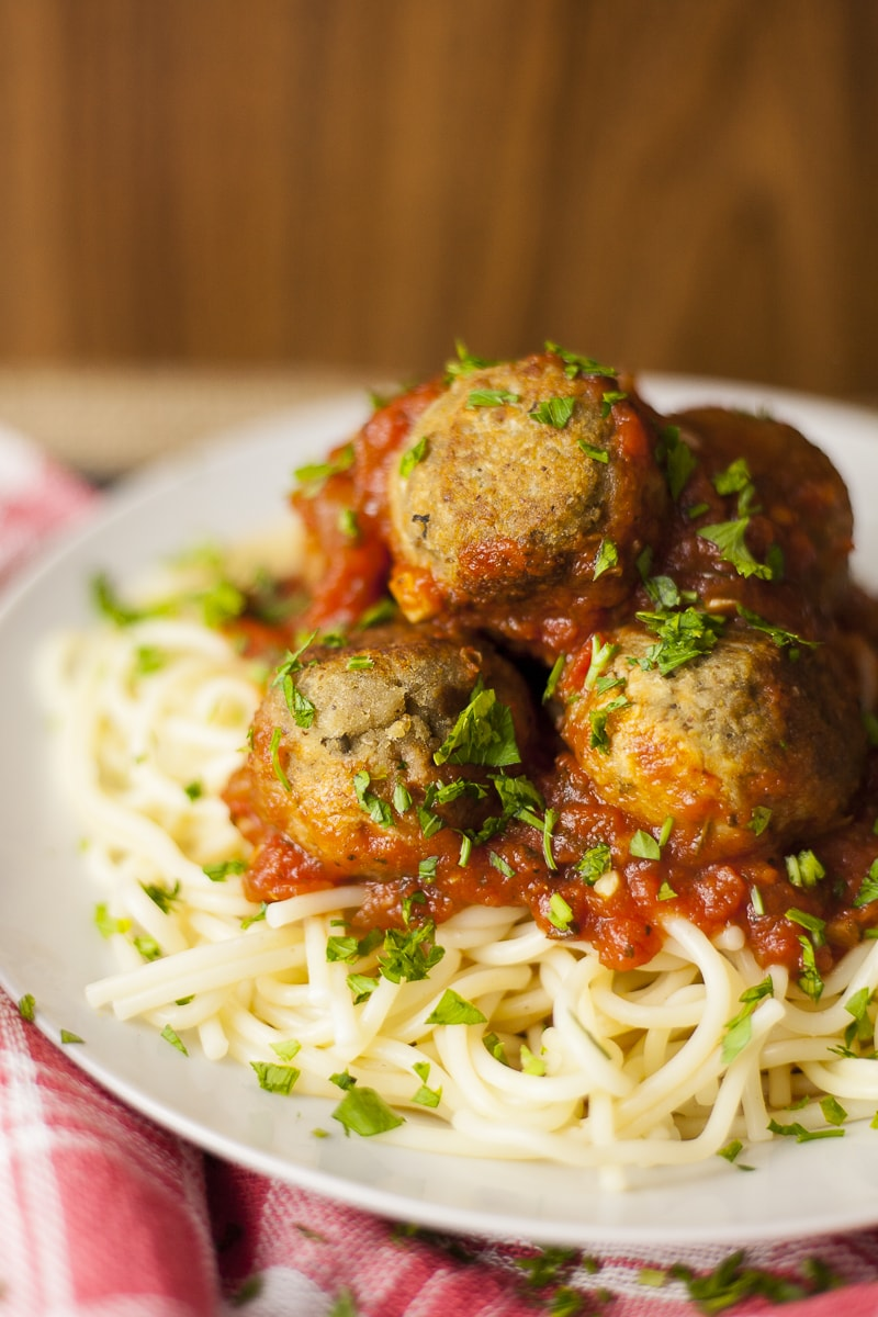 Spaghetti topped with marinara sauce and a couple of eggplant meatballs sprinkled with parsley