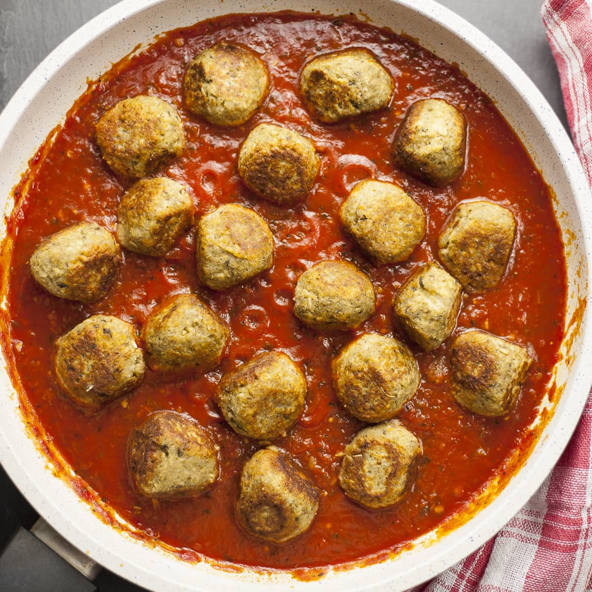 Overlay photo of a frying pan. Lot of small eggplant balls in marinara sauce