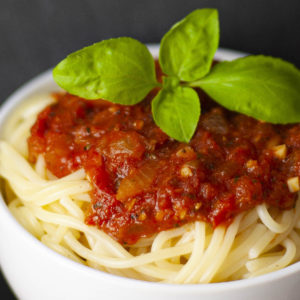 White bowl is full of spaghetti with red chunky pasta sauce and a couple of basil leaves on top.
