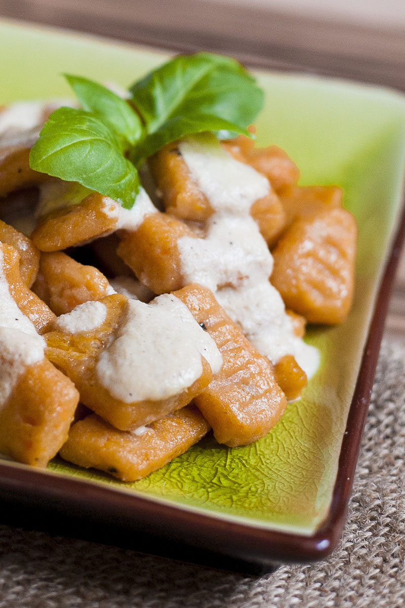 Orange rectangle pasta with white sauce on a green plate topped with fresh green basil leaves