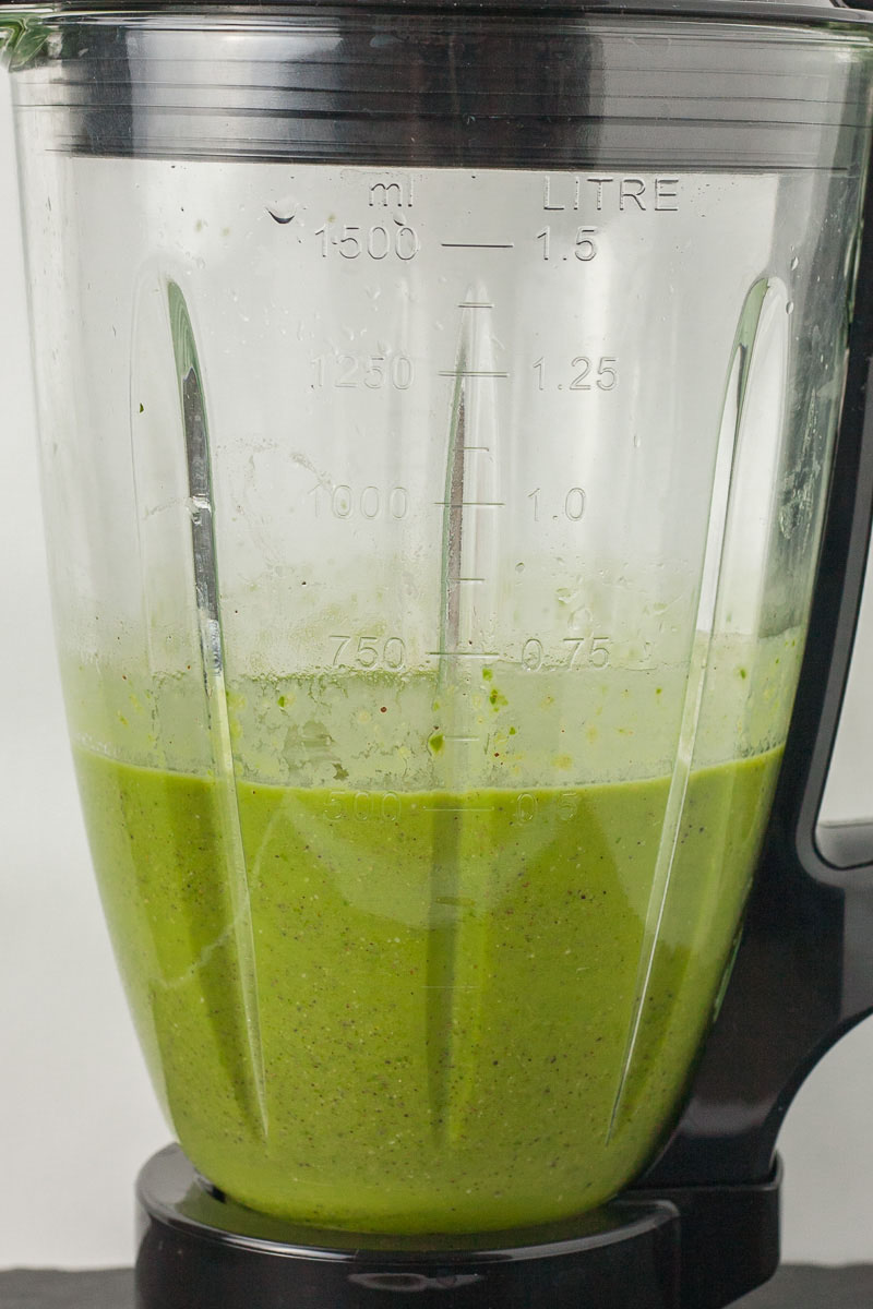 A blender is half full with a green liquid.