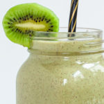 A large smoothie glass is filled with green liquid decorated with a kiwi slices and a black and gold straw. You can see 2 bananas and a couple of spinach leaves around it.
