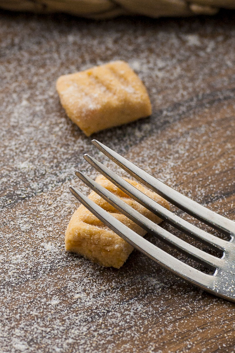 Soft orange rectangle-shaped pasta with a fork making a dent in it.