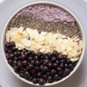 A white bowl on a light purple plate full of purple porridge topped with small grey seeds, almond slices and lots of purple blueberries