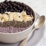 Close-up of a breakfast bowl with the finished Blueberry Millet Porridge. It is a purple porridge with 3 blueberry, some sliced almonds and chia seeds.