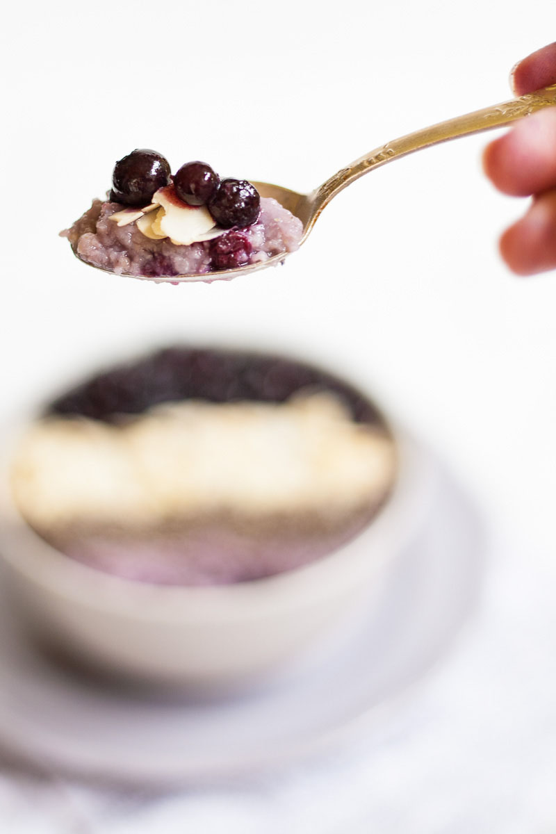 A spoon with purple porrdige and blueberries on top. A white bowl on a light purple plate full of purple porridge topped with small grey seeds, almond slices and lots of purple blueberries in the background