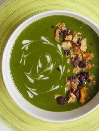 Close-up of a bowl full of vegan spinach soup sprinkled with vegetable crisps and dairy-free cream swirls.