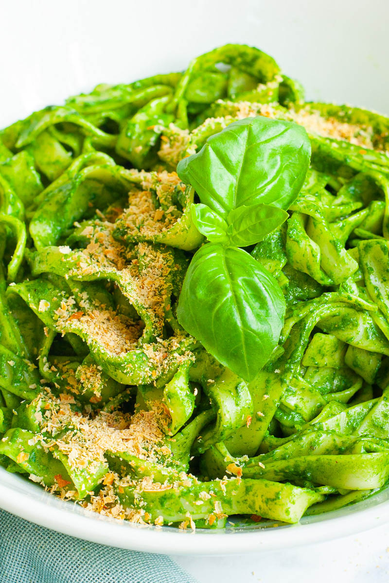 White bowl with fettuccine pasta covered in green sauces sprinkled with yellow flakes and a pair of basil leaves.