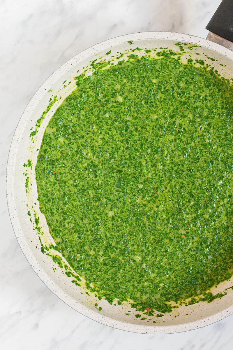A white frying pan from above with green sauce