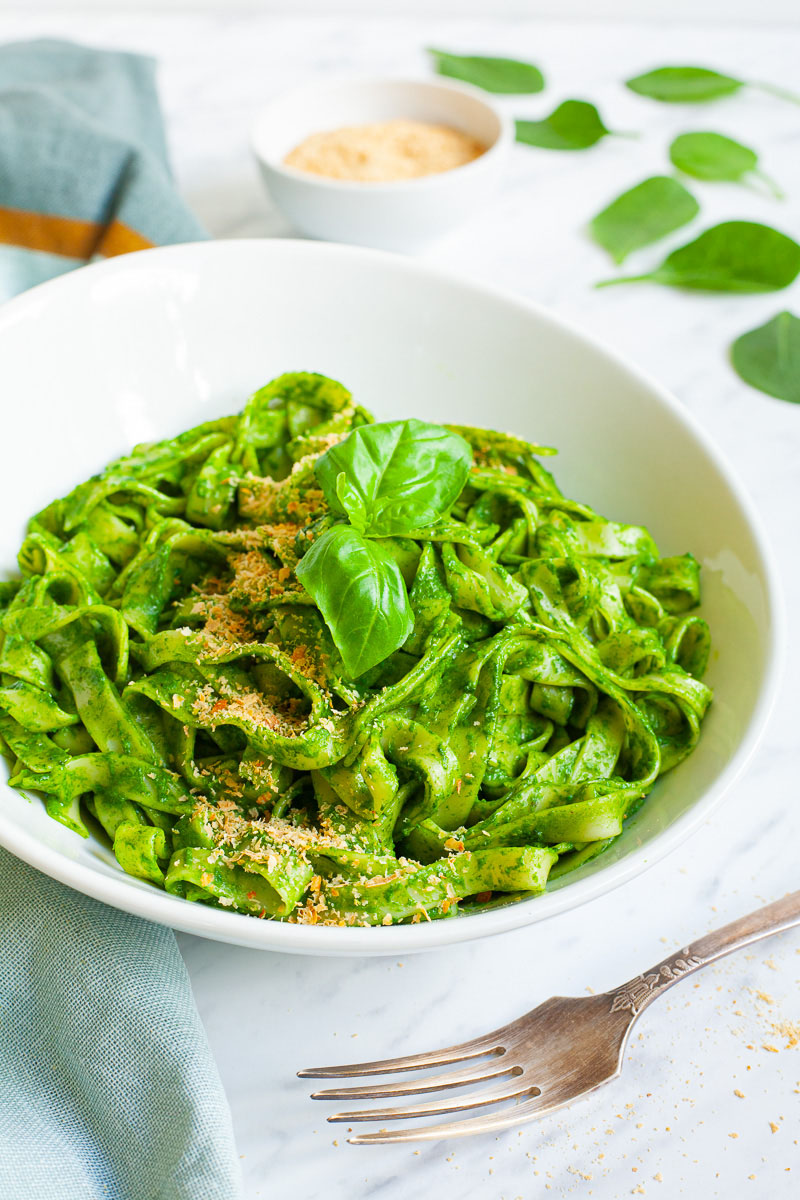 White bowl with fettuccine pasta covered in green sauces sprinkled with yellow flakes and a pair of basil leaves. A fork is next to the bowl.