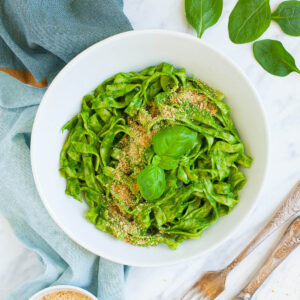 White bowl from above with fettuccine pasta covered in green sauces sprinkled with yellow flakes and a pair of basil leaves. A couple of leaves are scattered around. There is a small white bowl with more yellow flakes.