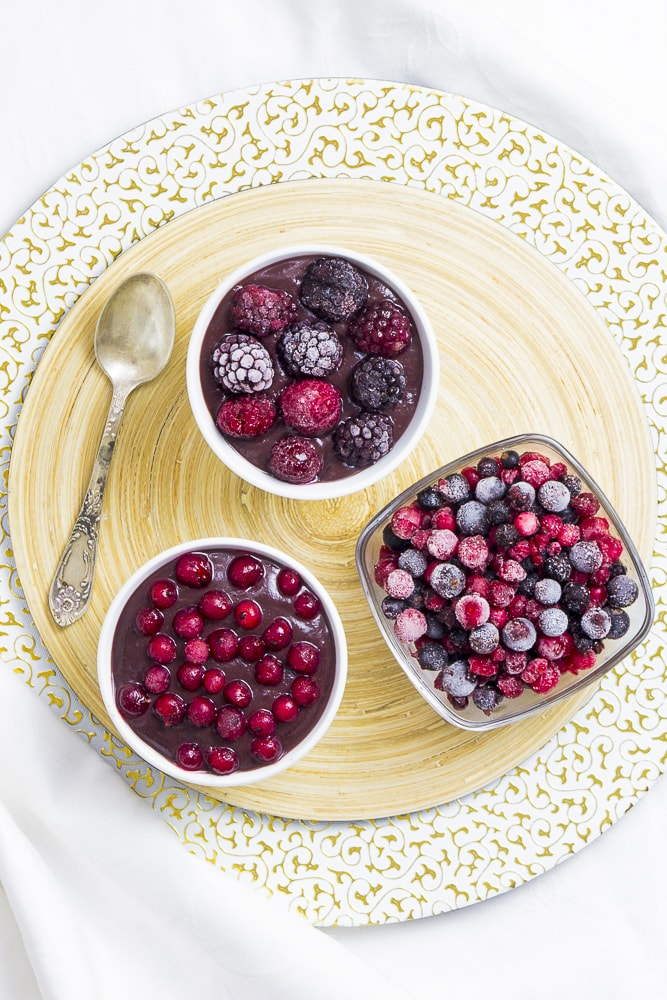 3 small bowl, one with vegan chocolate pudding topped with mixed berries, the other topped with red currant and one bowl is only fruits.