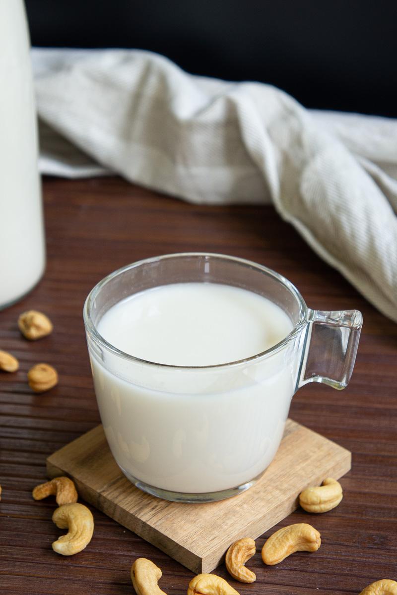 Glass of cashew milk on a wooden coaster. Cashews around.