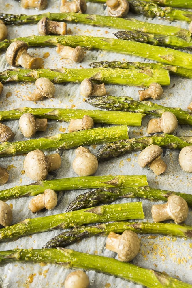 Close-up of roasted asparagus spears and small champion mushrooms on parchment paper