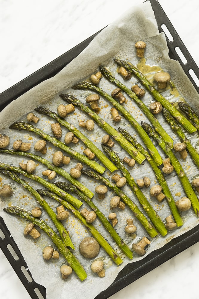 Black sheet pan full of roasted asparagus spears and small champion mushrooms on parchment paper