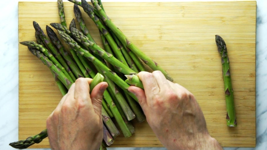 Close-up of how to snap asparagus stalk with hands above a wooden board full of fresh asparagus
