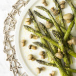 White plate with roasted asparagus and mushrooms styled as messy sprinkled with extra seasoning