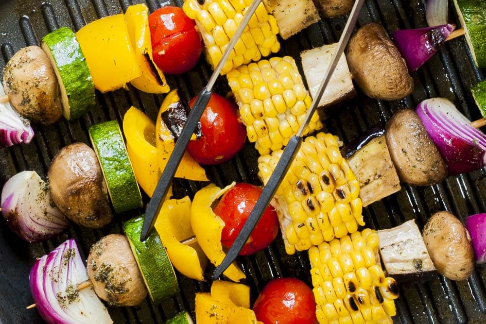 Close-up of the grilled vegetable kabobs in a grill pan with tongs