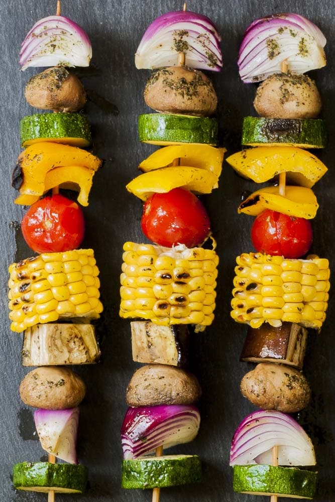 Close-up of 3 veggie skewers on a grey plate