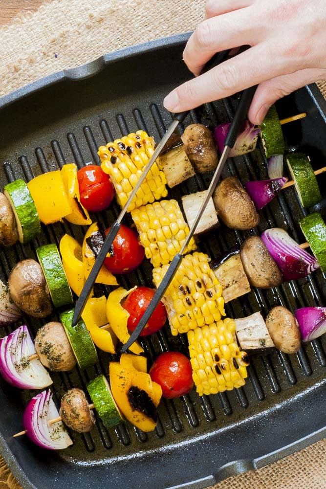 Close-up of grilled vegetable kabobs in a grill pan with tongs in hand