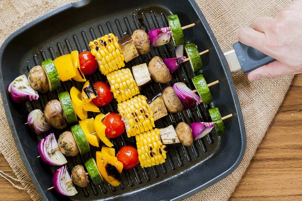 Close-up of 4 vegetable skewers in a grill pan