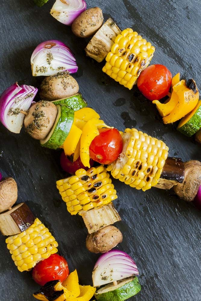 Close-up of grilled veggie kabobs on a grey plate