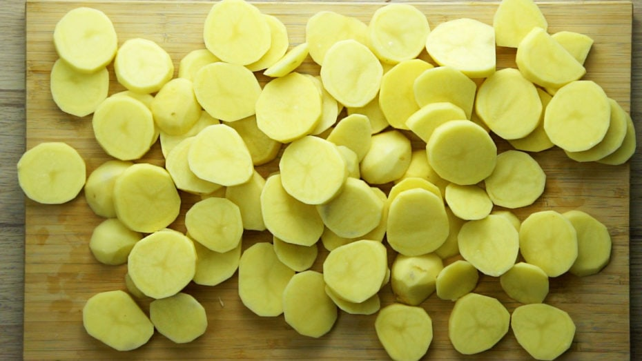 Raw potato slices on a wooden cutting board