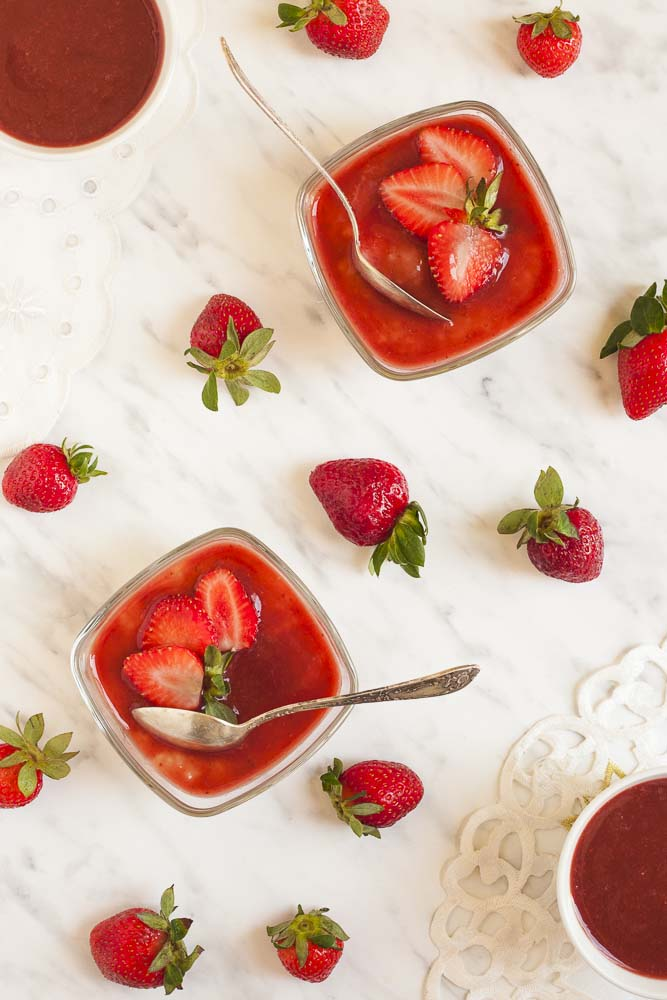 2 glass bowls of vegan tapioca pudding topped with strawberry puree from above. Scattered strawberries.