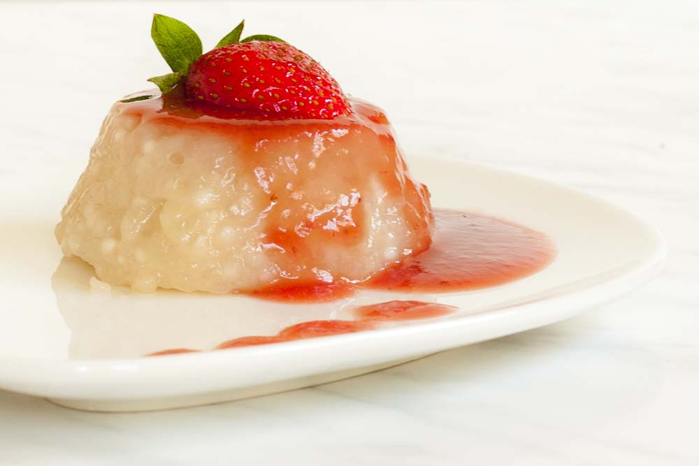 Tapioca pudding served as panna cotta topped with strawberry puree and fresh strawberries.