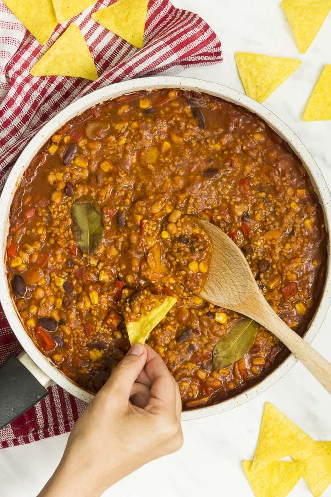 A pan full of loaded vegan bean chili with a wooden spoon in it and a hand dips a tortilla chips in it.