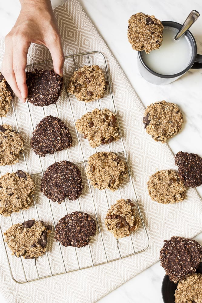 Overhead photo of several banana peanut butter oatmeal cookies on a wire rack. Some others are scattered around with a black mug of milk.