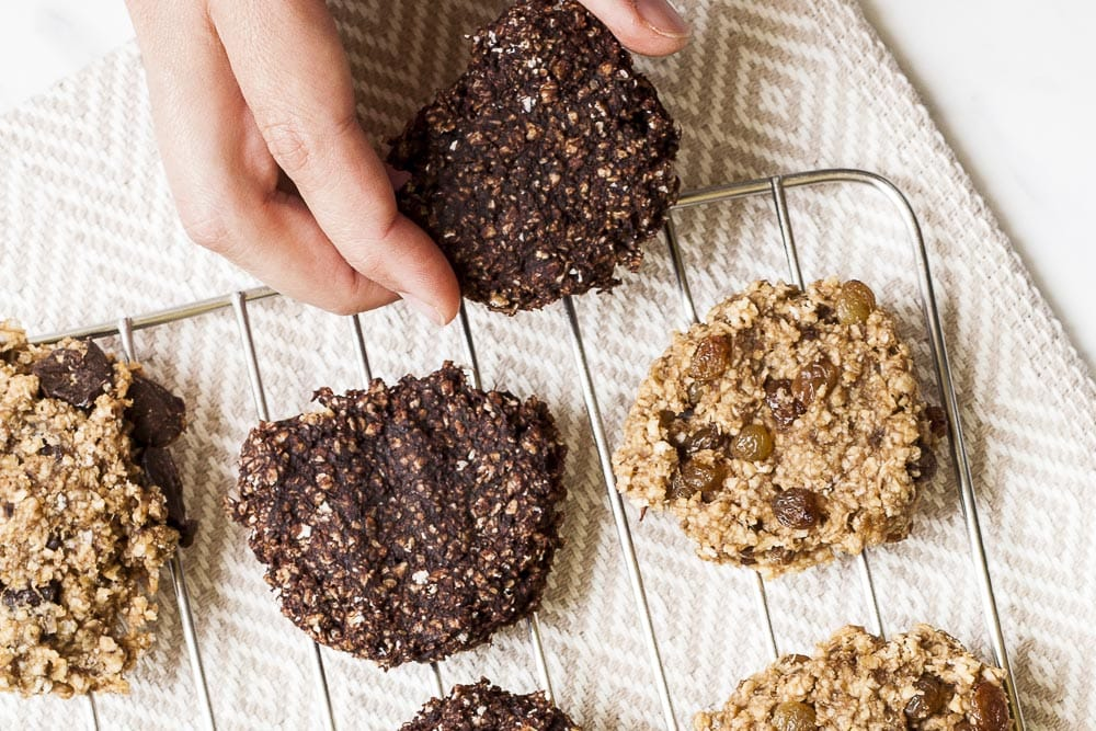 Several banana peanut butter oatmeal cookies on a cooling rack and a hand grabs one of them.