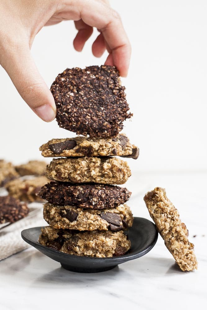 Banana Peanut Butter Oatmeal Cookie Stack where a hand grabs the top chocolate cookie.