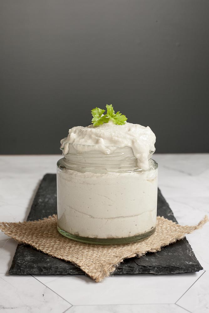 Small white glass packed with dairy-free sour cream and topped with fresh parsley.