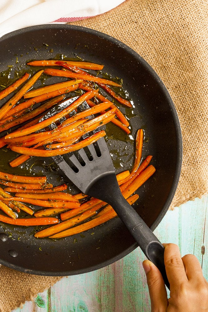 Frying pan from above with maple glazed sauteed julienne carrots.
