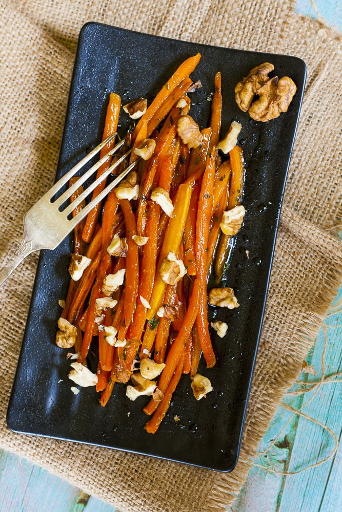 Maple galzed sauteed carrots with chopped walnuts on a black plate.