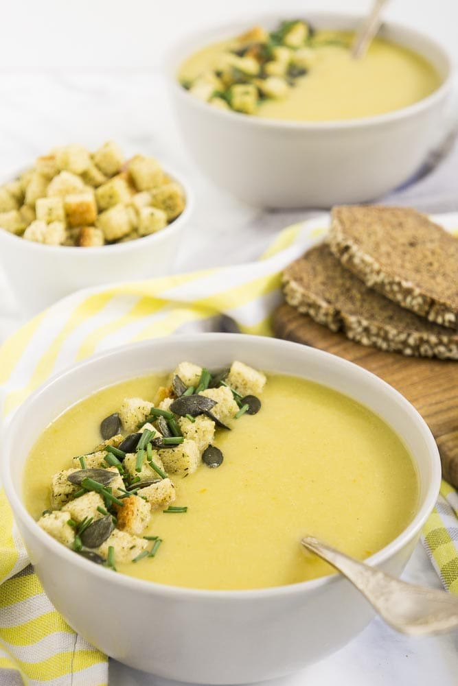 2 bowls of vegan cauliflower soup with spoon topped with croutons, pumpkin seeds and chives