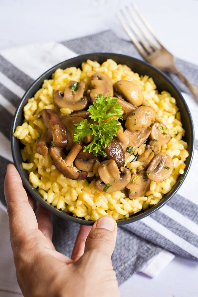 Black bowl of vegan mushroom risotto held by a hand in front of a grey-white napkin