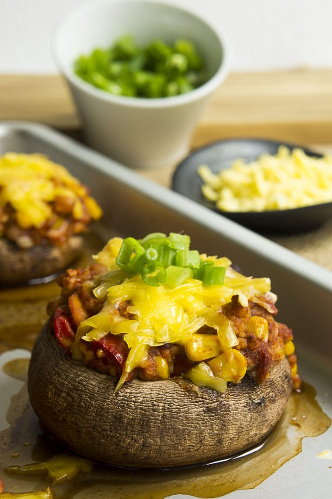 Close-up of a vegan stuffed portobello mushroom on the baking sheet with small bowls of grated cheese and chopped spring onion at the background